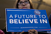 An attendee holds a campaign sign while listening to Senator Bernie Sanders an independent from Vermont and 2016 Democratic presidential candidate...
