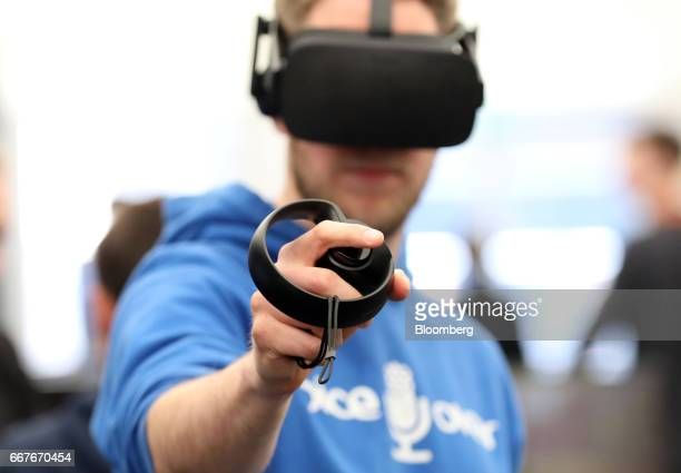 An attendee holds a control stick while testing an interactive virtual reality headset on the Advanced Micro Devices Inc stand at the Virtual Reality...