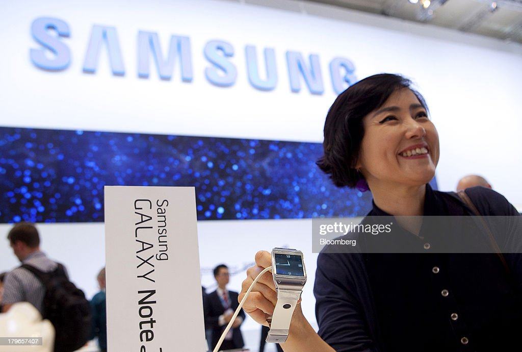 An attendee holds a Galaxy Gear smart watch device, manufactured by Samsung Electronics Co., at the IFA consumer electronics show in Berlin, Germany, on Friday, Sept. 6, 2013. Global smartphone revenue will rise 22 percent in 2013, or nearly half the pace of an expected 41 percent gain in shipments, amid falling prices, according to UBS. Photographer: Krisztian Bocsi/Bloomberg via Getty Images