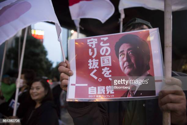 An attendee holds a poster showing Shinzo Abe Japan's prime minister and president of the Liberal Democratic Party during an election campaign rally...