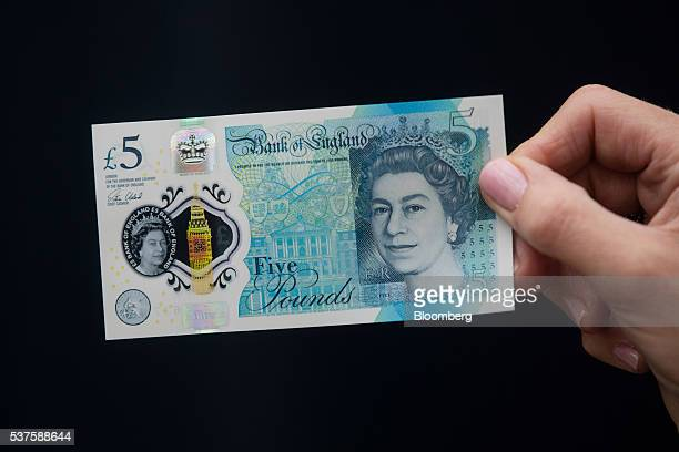 An attendee holds a sample of Britain's new 5pound polymer banknote at Blenheim Palace in Oxfordshire UK on Thursday June 2 2016 The Bank of...