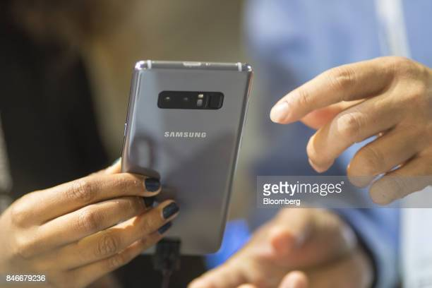 An attendee holds a Samsung Electronics Co Galaxy Note 8 smartphone displayed at the Mobile World Conference Americas event in San Francisco...