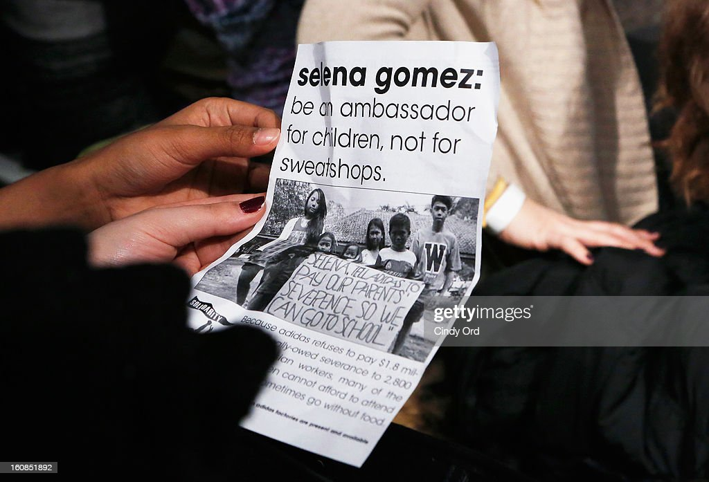 An attendee holds a USAS (United Students Against Sweatshops) flyer at the adidas NEO Label Fall 2013 fashion show on February 6, 2013 in New York City.