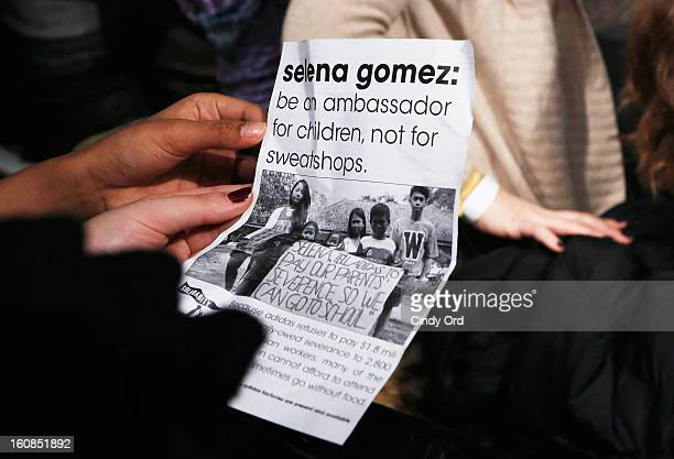 An attendee holds a USAS flyer at the adidas NEO Label Fall 2013 fashion show on February 6 2013 in New York City