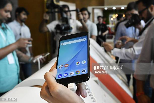 An attendee holds a Xiaomi Corp Mi A1 dual camera device during the smartphone's launch in New Delhi India on Tuesday Sept 5 2017 Google is teaming...