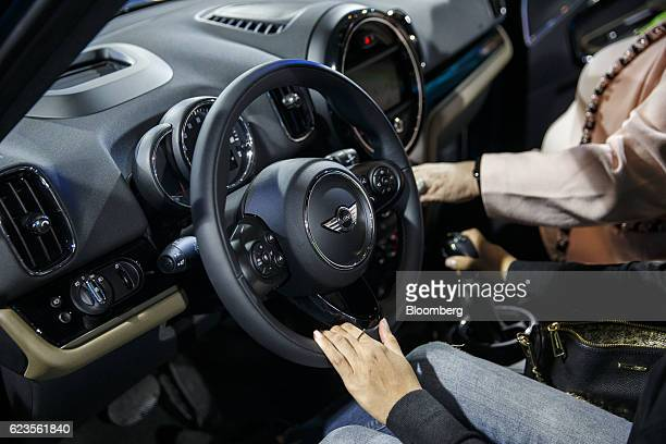 An attendee holds the steering wheel of the Bayerische Motoren Werke AG MINI Countryman compact sports utility vehicle during an event in Los Angeles...