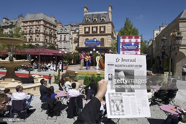 An attendee holds up a fake newspaper with the headline 'inauguration of the bistrot Chez Remy' as musicians perform during the inauguration of the...