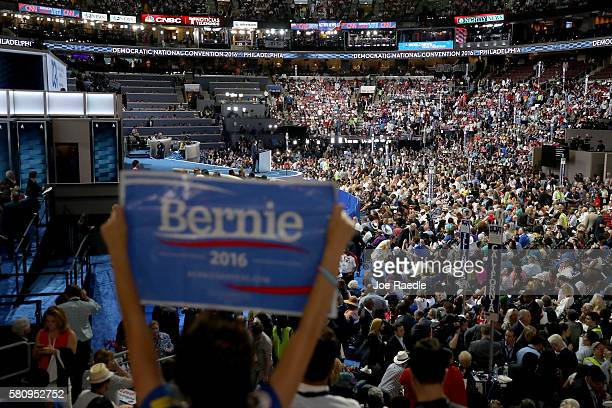 An attendee holds up a sign in support Sen Bernie Sanders as Gov Dan Malloy delivers a speech on the first day of the Democratic National Convention...
