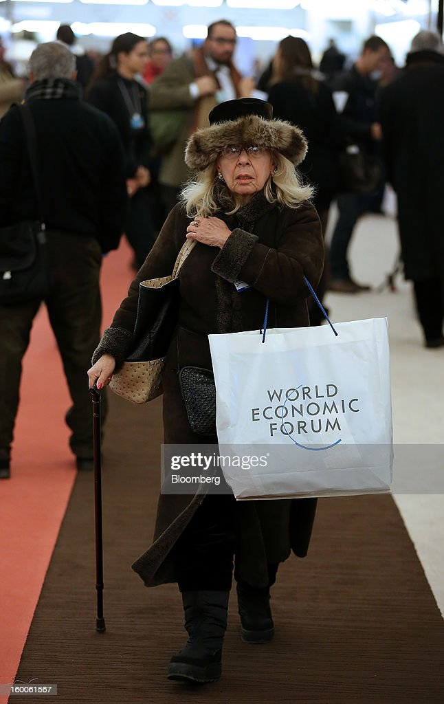 An attendee in a winter coat and hat arrives at the Congress Center on day three of the World Economic Forum (WEF) in Davos, Switzerland, on Friday, Jan. 25, 2013. World leaders, influential executives, bankers and policy makers attend the 43rd annual meeting of the World Economic Forum in Davos, the five day event runs from Jan. 23-27. Photographer: Simon Dawson/Bloomberg via Getty Images