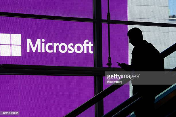 An attendee is silhouetted against a Microsoft Corp poster as he rides an escalator at the Microsoft Developers Build Conference in San Francisco...