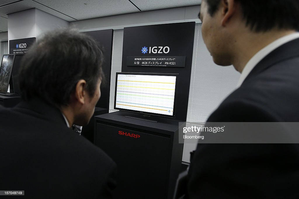 An attendee, left, examines a Sharp Corp. PN-K321, 32-inch 4K2K liquid crystal display (LCD) IGZO monitor with an employee during the unveiling in Tokyo, Japan, on Wednesday, Nov. 28, 2012. Sharp, Japan's largest maker of liquid-crystal displays, has lined up customers for its most advanced panels after saying earlier this year it was struggling to find buyers. Photographer: Kiyoshi Ota/Bloomberg via Getty Images