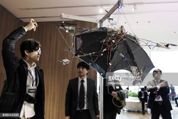 An attendee left looks at a prototype of an Asahi Power Service Inc free Parasol a handleless flying umbrella at a SoftBank Corp Style media event in...