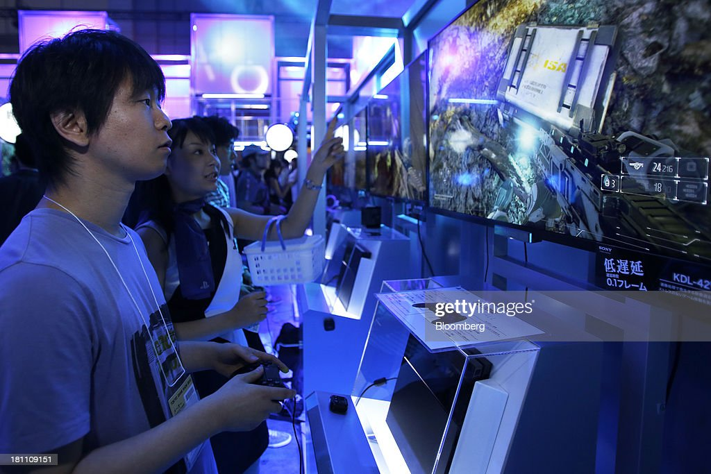 An attendee, left, plays a video game on a Sony Computer Entertainment Inc. PlayStation 4 (PS4) video game console next to a booth attendant at the Tokyo Game Show 2013 in Chiba, Japan, on Thursday, Sept. 19, 2013. Sony Corp. expects sales of its new PlayStation 4 console to reach 5 million units this financial year, with at least 20 games to be available as it competes with a new machine from Microsoft Corp. Photographer: Kiyoshi Ota/Bloomberg via Getty Images