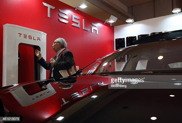 An attendee looking at a battery charger is reflected on a Tesla Motors Inc Model S electric vehicle displayed at the 43rd Tokyo Motor Show 2013 in...