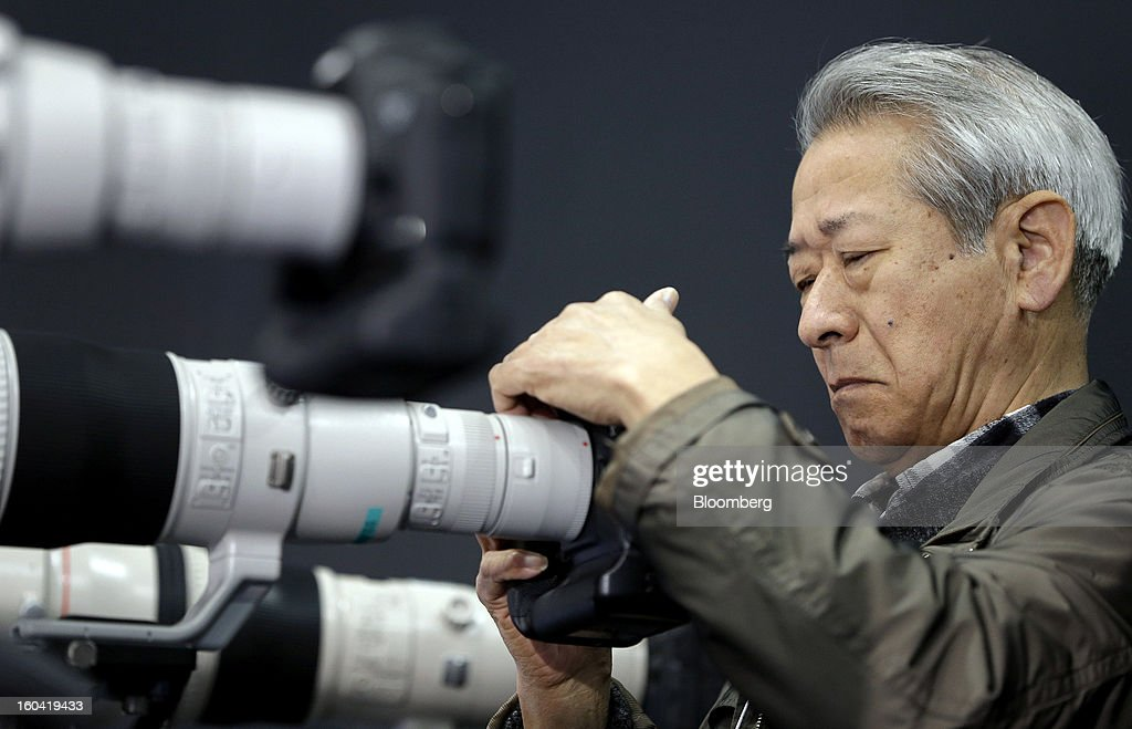 An attendee looks at a Canon Inc. digital single lens reflex (DSLR) camera mounted to a 600mm telephoto lens intern coupled to a 'two times' converter during the CP+ Camera and Photo Imaging Show in Yokohama City, Japan, on Thursday, Jan. 31, 2013. The CP+ Camera and Photo Imaging Show runs from Jan. 31 to Feb. 3. Photographer: Kiyoshi Ota/Bloomberg via Getty Images
