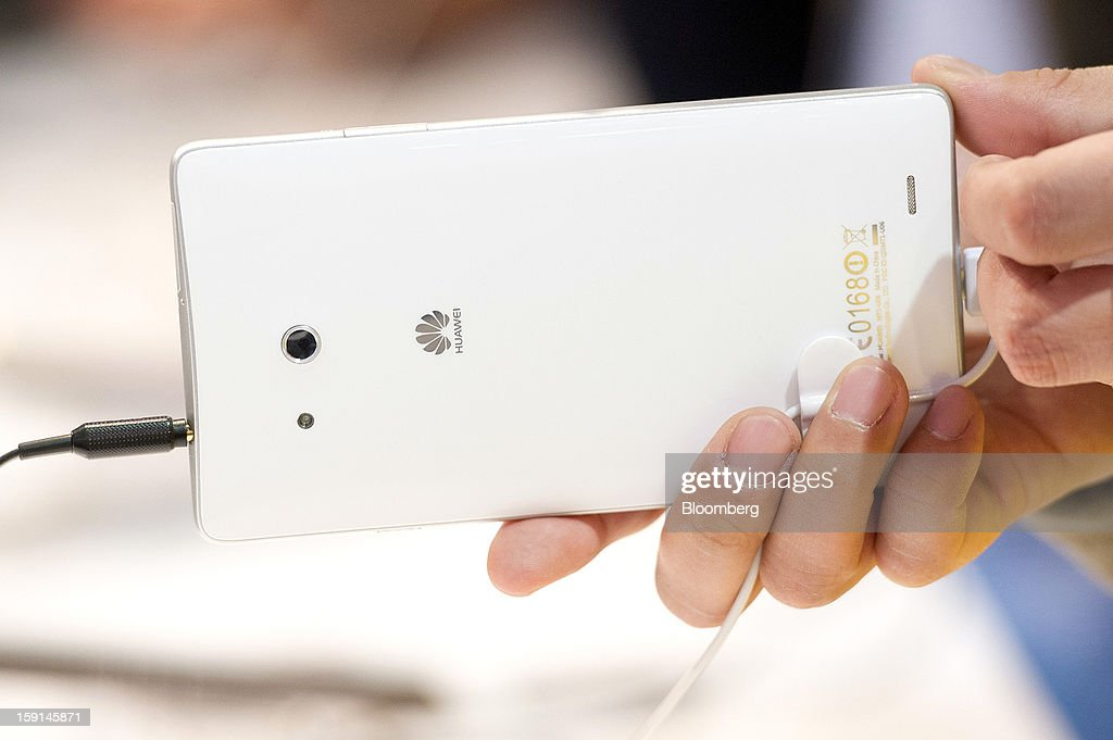 An attendee looks at a Huawei Technologies Co. Ascend Mate smartphone at the 2013 Consumer Electronics Show in Las Vegas, Nevada, U.S., on Tuesday, Jan. 8, 2013. The 2013 CES trade show, which runs until Jan. 11, is the world's largest annual innovation event that offers an array of entrepreneur focused exhibits, events and conference sessions for technology entrepreneurs. Photographer: David Paul Morris/Bloomberg via Getty Images