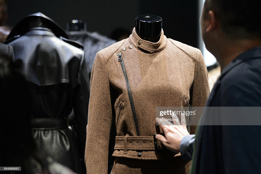 An attendee looks at a jacket displayed during a preview of Fast Retailing Co.'s Uniqlo 2016 Fall-Winter lineup in Tokyo, Japan, on Wednesday, May 25, 2016. Analysts and investors will be watching as Uniqlo unveils the new season's LifeWear line in Tokyo to see whether Chairman Tadashi Yanai will come through with his pledge to offer the 'lowest possible prices.' Photographer: Akio Kon/Bloomberg via Getty Images
