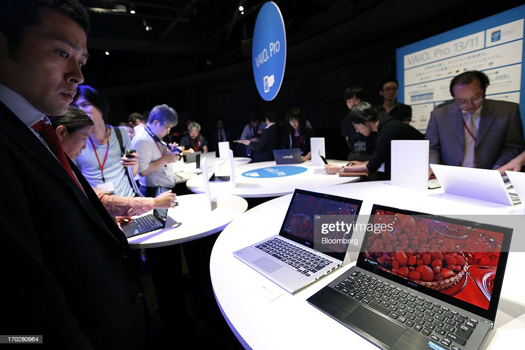 An attendee looks at a Sony Corp. Vaio Pro Ultrabook laptop computer, right, during a product launch in Tokyo, Japan, on Monday, June 10, 2013. Sony Corp. is Japan's biggest consumer-electronics exporter. Photographer: Kiyoshi Ota/Bloomberg via Getty Images