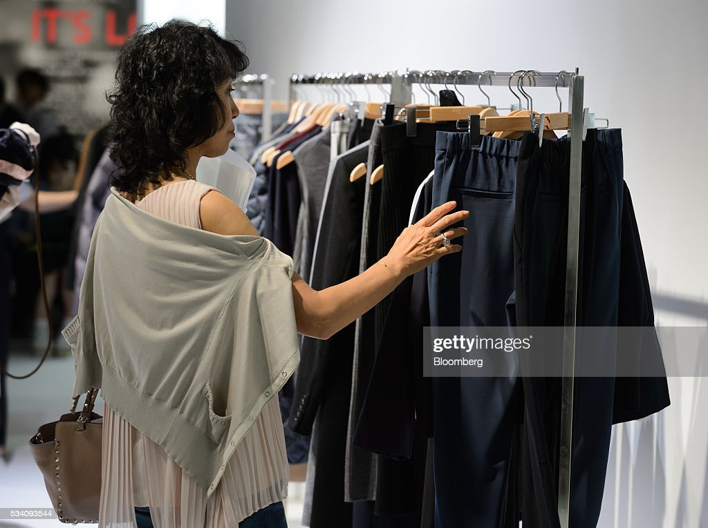 An attendee looks at clothing items displayed during a preview of Fast Retailing Co.'s Uniqlo 2016 Fall-Winter lineup in Tokyo, Japan, on Wednesday, May 25, 2016. Analysts and investors will be watching as Uniqlo unveils the new season's LifeWear line in Tokyo to see whether Chairman Tadashi Yanai will come through with his pledge to offer the 'lowest possible prices.' Photographer: Akio Kon/Bloomberg via Getty Images