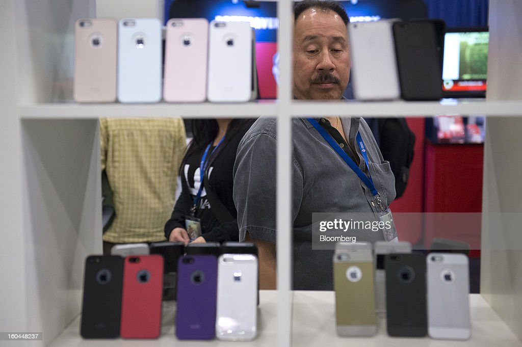 An attendee looks at covers for Apple Inc. iPhones at the Macworld/iWorld conference at the Moscone Center West in San Francisco, California, U.S., on Thursday, Jan. 31, 2013. This year's conference, titled 'The Ultimate iFANEvent,' brings together attendees to celebrate Apple Inc. technology and learn more about products and services for Apple users. Photographer: David Paul Morris/Bloomberg via Getty Images