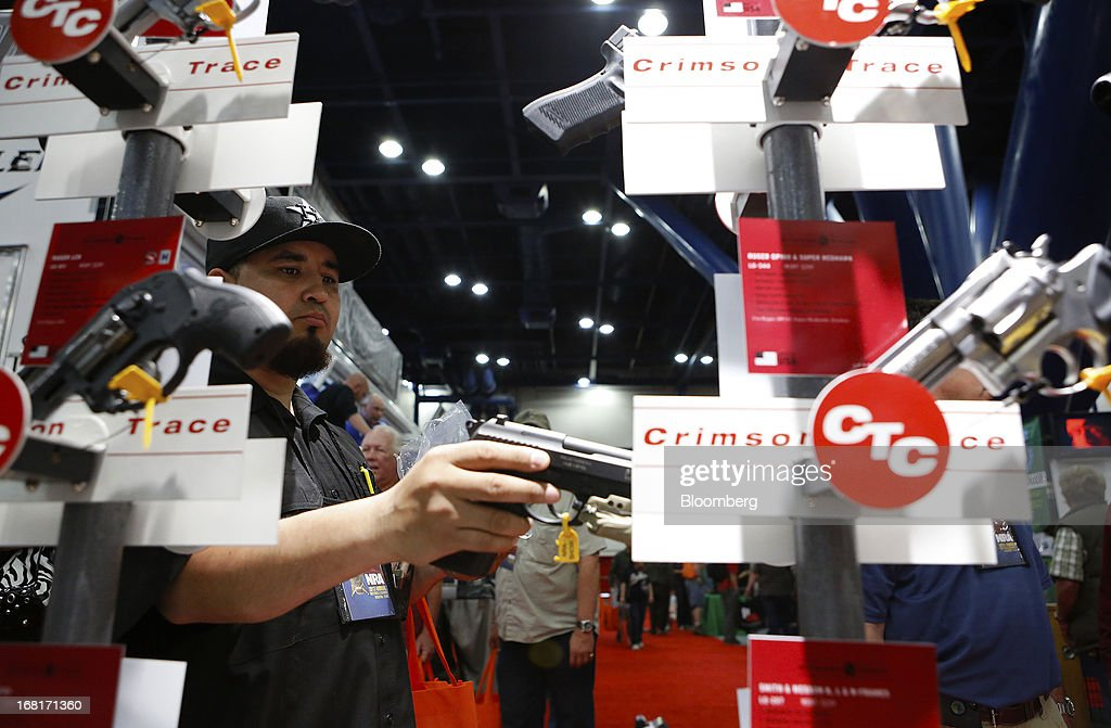 An attendee looks at handguns with laser sights made by Crimson Trace during the 2013 National Rifle Association (NRA) Annual Meetings & Exhibits at the George R. Brown Convention Center in Houston, Texas, U.S., on Saturday, May 4, 2013. After the U.S. Senate defeated a proposed expansion of background checks on gun purchases, the NRA's annual conference has a celebratory atmosphere. Yet as the festivities began, gun-control advocates swarmed town halls, organizing petitions and buying local ads to pressure senators from Alaska to New Hampshire to reconsider the measure that failed by six votes on April 17. Photographer: Aaron M. Sprecher/Bloomberg via Getty Images