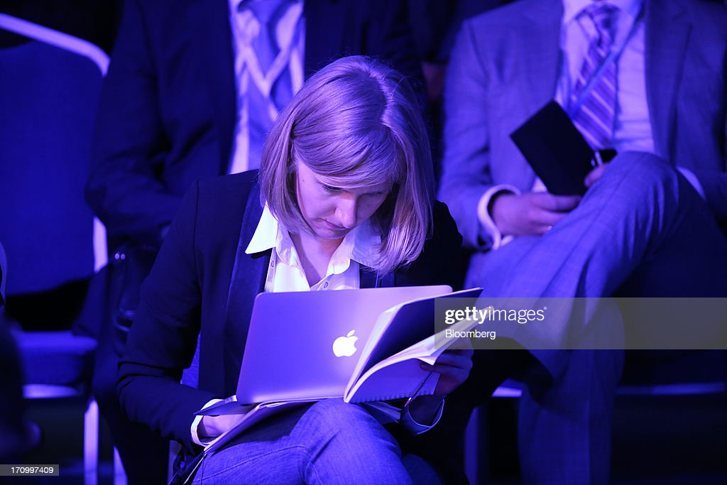 An attendee looks at her Apple Inc. laptop computer during a conference session on the opening day of the St. Petersburg International Economic Forum 2013 (SPIEF) in St. Petersburg, Russia, on Thursday, June 20, 2013. Russian consumer spending probably eased and investment shrank at the fastest pace since 2011, adding to evidence the $2 trillion economy is stalling. Photographer: Andrey Rudakov/Bloomberg via Getty Images
