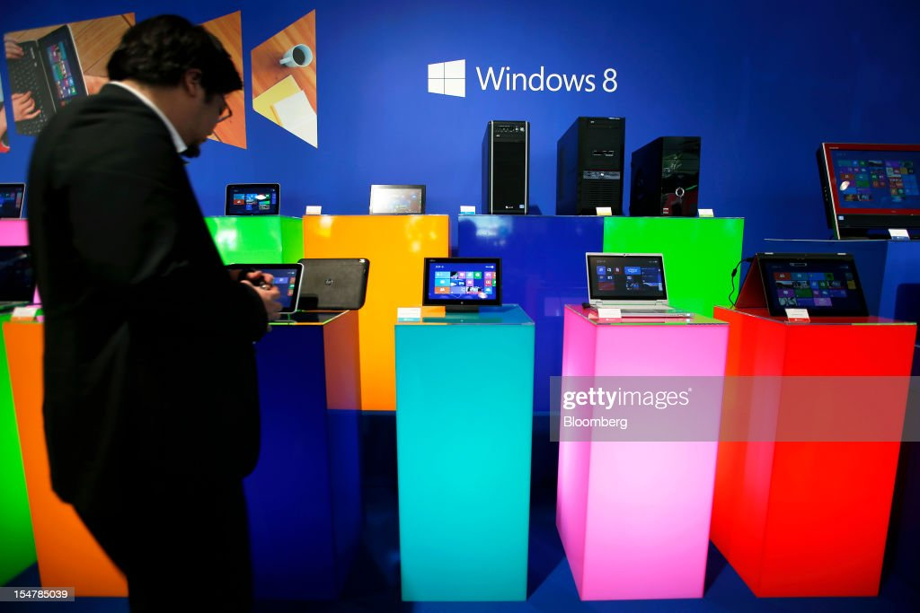 An attendee looks at tablet devices and laptop computers running Microsoft Corp's Windows 8 operating system during a launch event in Tokyo Japan on...