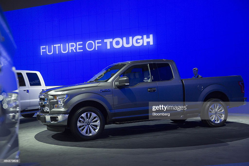 An attendee looks at the Ford Motor Co. F-150 pickup truck during the Washington Auto Show in Washington, D.C., U.S., on Wednesday, Jan. 22, 2014. After laboring for five years to develop its aluminum F-150, Ford Motor Co. now confronts a new challenge: preventing higher insurance rates and a dearth of mechanics equipped to repair its body from deterring buyers. Photographer: Andrew Harrer/Bloomberg via Getty Images