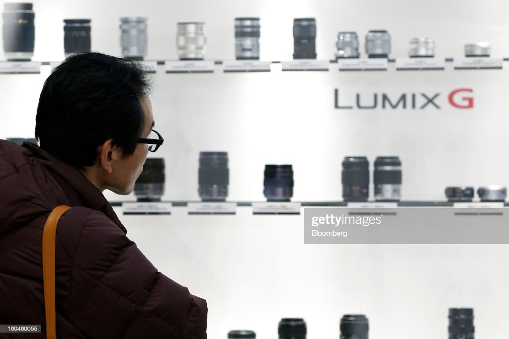 An attendee looks at the line-up of micro four-thirds lenses for Panasonic Corp. Lumix G-series digital cameras at the CP+ Camera and Photo Imaging Show in Yokohama City, Japan, on Thursday, Jan. 31, 2013. Panasonic, Japan's second-biggest television maker, reported an unexpected third-quarter profit because of a weaker yen and restructuring efforts. Photographer: Kiyoshi Ota/Bloomberg via Getty Images
