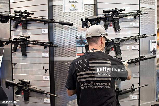 An attendee looks over rifles in the ArmaLite Inc booth on the exhibition floor of the 144th National Rifle Association Annual Meetings and Exhibits...