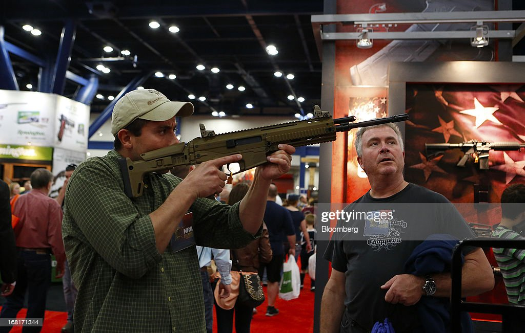An attendee looks through the scope of a Freedom Group Inc. Bushmaster brand assault rifle during the 2013 National Rifle Association (NRA) Annual Meetings & Exhibits at the George R. Brown Convention Center in Houston, Texas, U.S., on Saturday, May 4, 2013. After the U.S. Senate defeated a proposed expansion of background checks on gun purchases, the NRA's annual conference has a celebratory atmosphere. Yet as the festivities began, gun-control advocates swarmed town halls, organizing petitions and buying local ads to pressure senators from Alaska to New Hampshire to reconsider the measure that failed by six votes on April 17. Photographer: Aaron M. Sprecher/Bloomberg via Getty Images