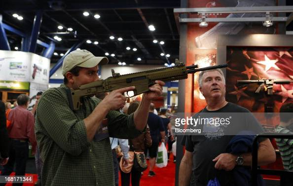 An attendee looks through the scope of a Freedom Group Inc Bushmaster brand assault rifle during the 2013 National Rifle Association Annual Meetings...