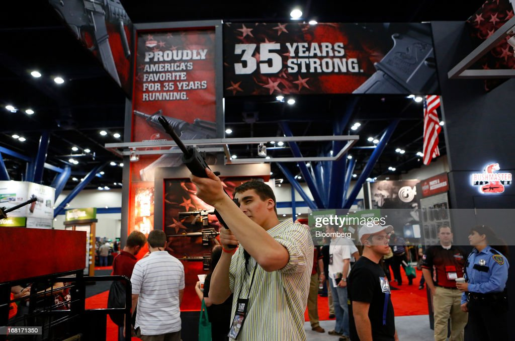 An attendee looks through the scope of a Freedom Group Inc. Bushmaster rifle during the 2013 National Rifle Association (NRA) Annual Meetings & Exhibits at the George R. Brown Convention Center in Houston, Texas, U.S., on Saturday, May 4, 2013. After the U.S. Senate defeated a proposed expansion of background checks on gun purchases, the NRA's annual conference has a celebratory atmosphere. Yet as the festivities began, gun-control advocates swarmed town halls, organizing petitions and buying local ads to pressure senators from Alaska to New Hampshire to reconsider the measure that failed by six votes on April 17. Photographer: Aaron M. Sprecher/Bloomberg via Getty Images