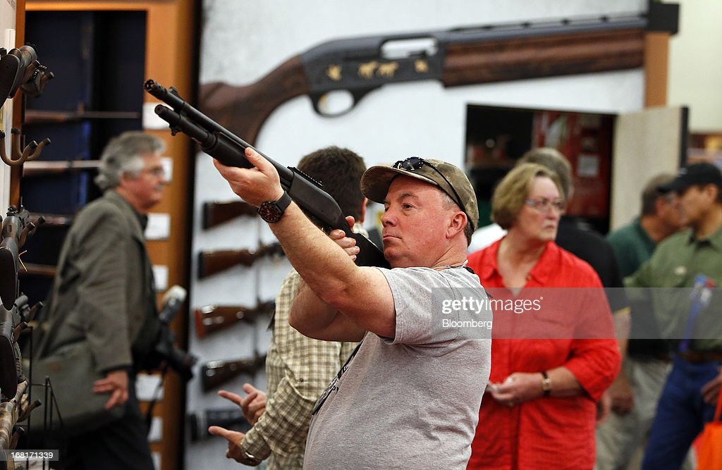 An attendee looks through the scope of a Freedom Group Inc. Remington brand gun during the 2013 National Rifle Association (NRA) Annual Meetings & Exhibits at the George R. Brown Convention Center in Houston, Texas, U.S., on Saturday, May 4, 2013. After the U.S. Senate defeated a proposed expansion of background checks on gun purchases, the NRA's annual conference has a celebratory atmosphere. Yet as the festivities began, gun-control advocates swarmed town halls, organizing petitions and buying local ads to pressure senators from Alaska to New Hampshire to reconsider the measure that failed by six votes on April 17. Photographer: Aaron M. Sprecher/Bloomberg via Getty Images