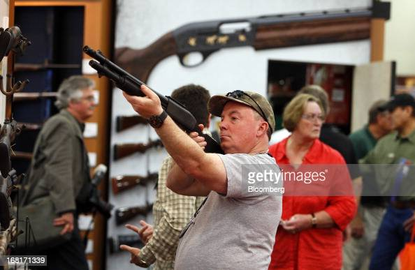 An attendee looks through the scope of a Freedom Group Inc Remington brand gun during the 2013 National Rifle Association Annual Meetings Exhibits at...