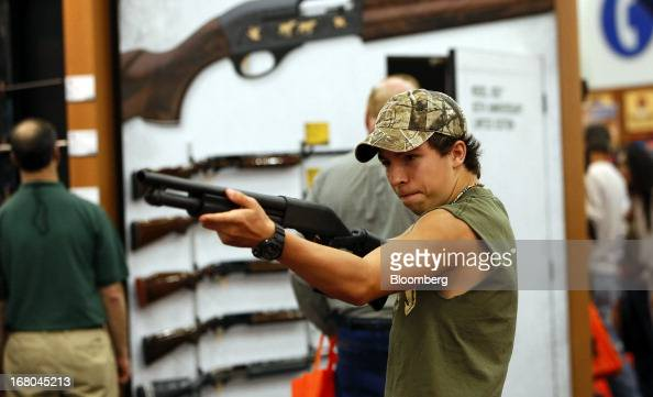 An attendee looks through the scope of a Remington gun during the 2013 National Rifle Association Annual Meetings Exhibits at the George R Brown...