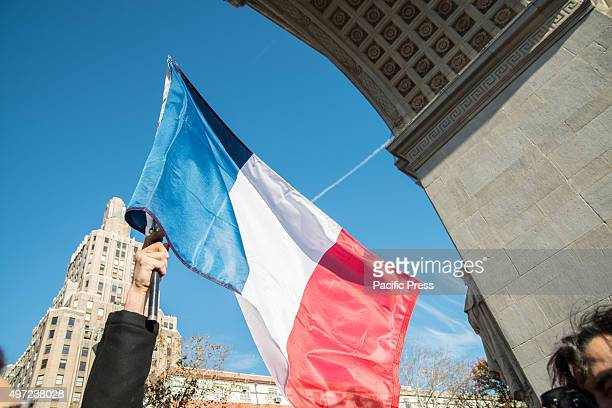 An attendee of the mass vigil for the Paris attack victims in Washington Square Park holds aloft the French tricolor flag while standing under the...