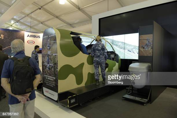 An attendee operates a Lockheed Martin Co Target Sight System while seated in a Textron Inc Bell Helicopter AH1Z Viper simulator in the Lockheed...
