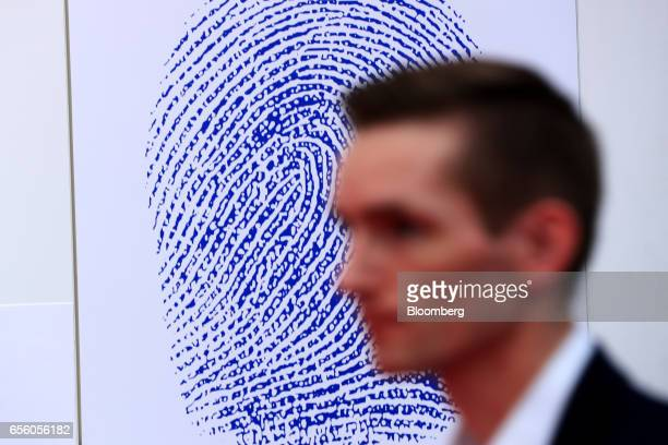 An attendee passes a large fingerprint motif on a display wall at the Dermalog Identification Systems GmbH pavilion at the CeBIT 2017 tech fair in...