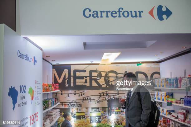 An attendee passes in front of a display during the initial public offering of Atacadao SA the Brazilian unit of French retailerCarrefour SA at...