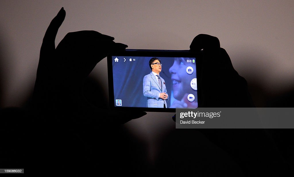 An attendee photographs Samsung Electronics President Boo-Keun Yoon as he speaks during a press event at the Mandalay Bay Convention Center for the 2013 International CES on January 7, 2013 in Las Vegas, Nevada. CES, the world's largest annual consumer technology trade show, runs from January 8-11 and is expected to feature 3,100 exhibitors showing off their latest products and services to about 150,000 attendees.