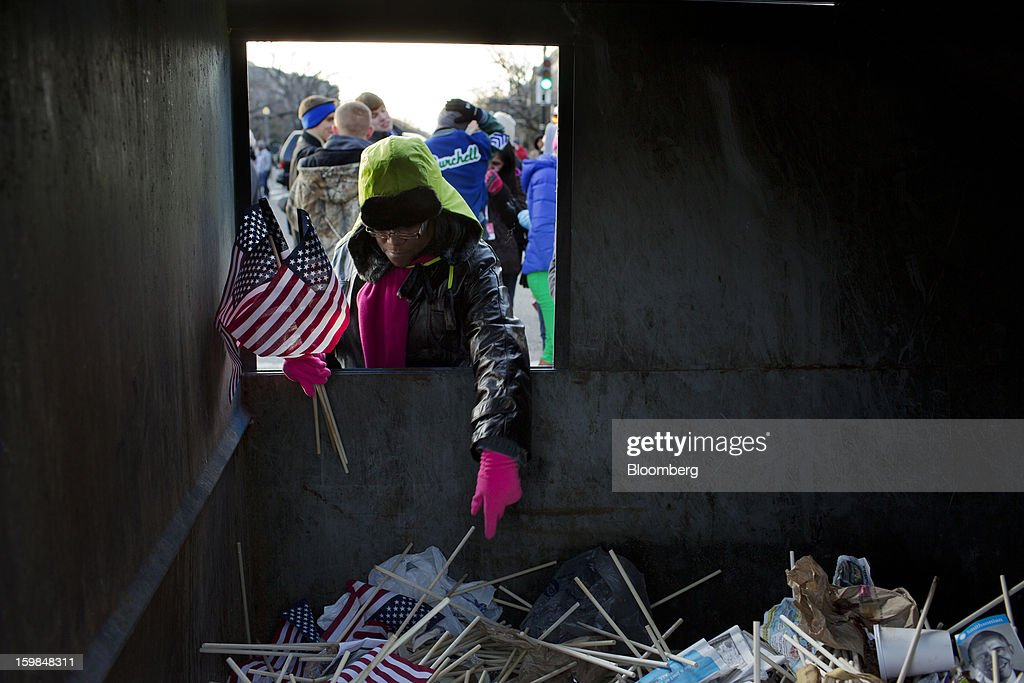 An attendee picks discarded American flags out of a dumpster during the U.S. presidential inauguration in Washington, D.C., U.S., on Monday, Jan. 21, 2013. A crowd estimated by police to be as large as 700,000, including warmly dressed women with American flags stuck in their hair, a smattering of celebrities and many Republicans, gathered today to witness President Barack Obama take his second oath of office on the steps of the U.S. Capitol. Photographer: Victor J. Blue/Bloomberg via Getty Images