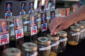 An attendee places a corn kernel into a jar to vote for 2016 Republican presidential candidate Donald Trump in a television news station's 'cast your...