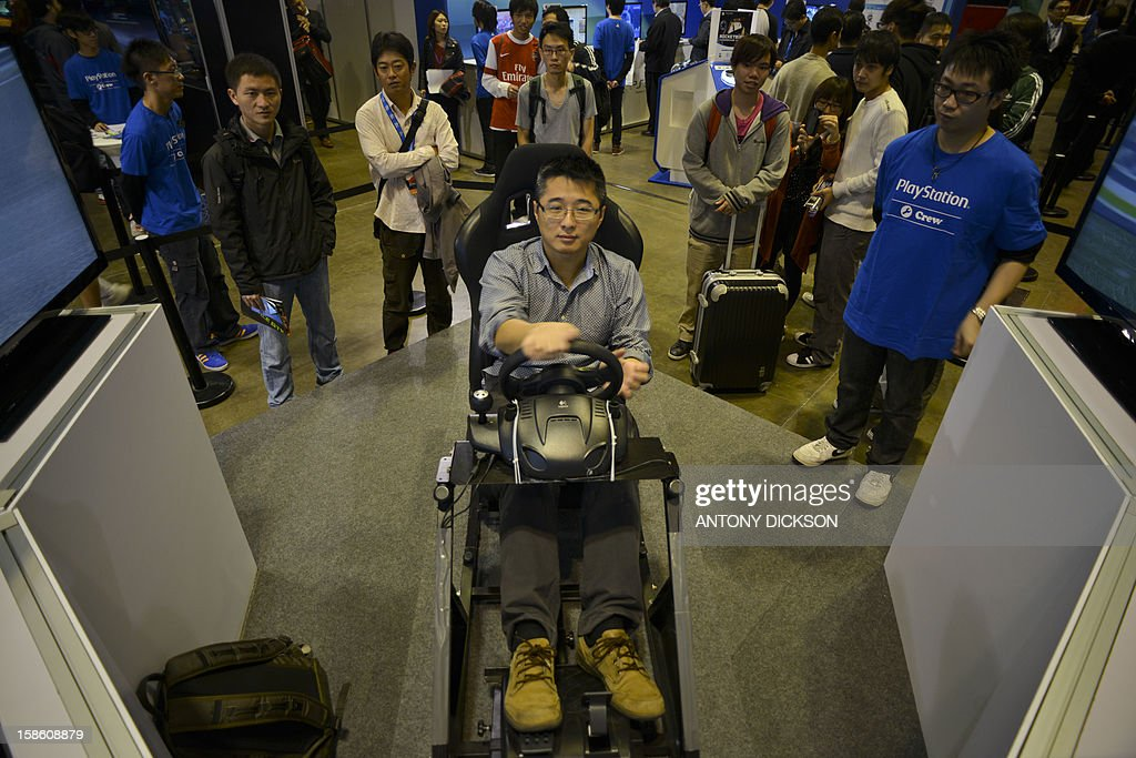 An attendee (C) plays a Sony Playstation driving game during the Asia Game Show (AGS) in Hong Kong on December 21, 2012. The AGS is highlighting products from the electronic gaming industry and runs from December 21 to 24. AFP PHOTO / Antony DICKSON
