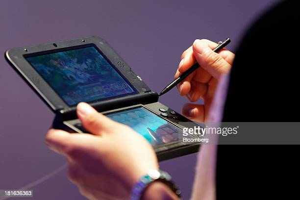 An attendee plays a video game on a Nintendo Co 3DS handheld game player in the GungHo Online Entertainment Inc booth at the Tokyo Game Show 2013 in...