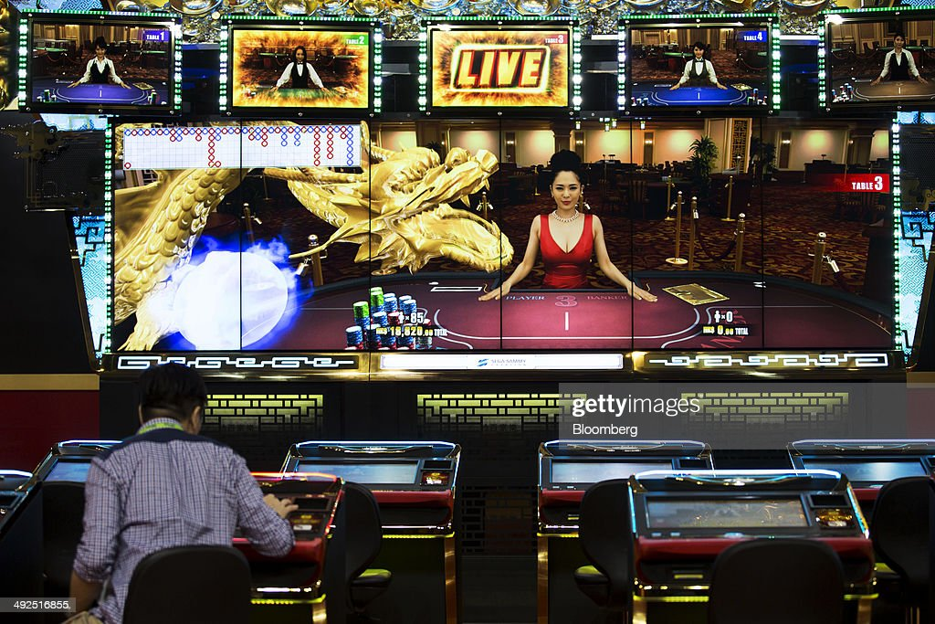 An attendee plays baccarat at the Sega Sammy Holdings Inc. booth at the Global Gaming Expo (G2E) inside the Venetian Macao resort and casino, operated by Sands China Ltd., a unit of Las Vegas Sands Corp., in Macau, China, on Tuesday, May 20, 2014. The gaming expo runs through May 22. Photographer: Brent Lewin/Bloomberg via Getty Images