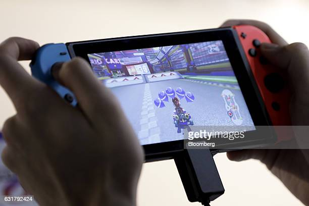 An attendee plays the 'Mario Kart 8 Deluxe' video game on a Nintendo Co Switch game console during an unveiling event in Tokyo Japan on Friday Jan 13...