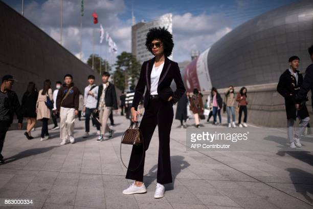 TOPSHOT An attendee poses for a photo during Seoul Fashion Week at Dongdaemun Design Plaza in Seoul on October 19 2017 For Seoul's flamboyant...