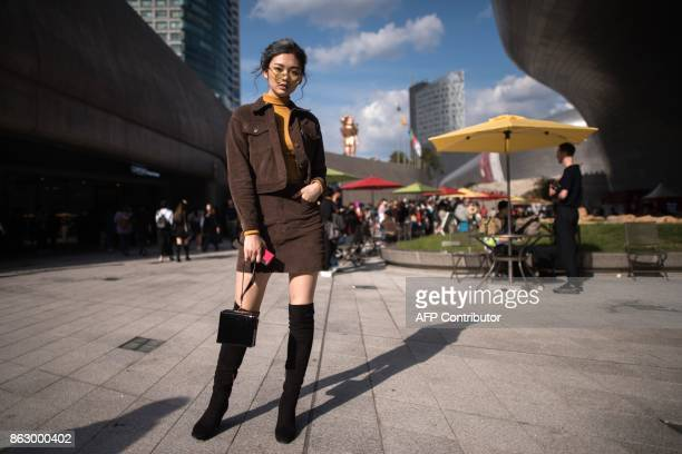 An attendee poses for a photo during Seoul Fashion Week at Dongdaemun Design Plaza in Seoul on October 19 2017 For Seoul's flamboyant followers of...