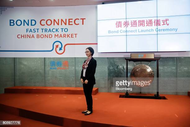 An attendee poses for a photograph in front of signage for the ChinaHong Kong Bond Connect at the Hong Kong Stock Exchange in Hong Kong China on...